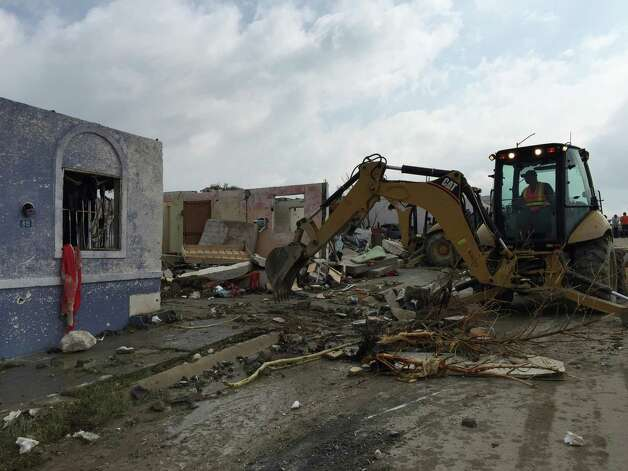 "A bulldozer cleans up debris after a powerful tornado swept past in Ciudad Acuna, northern Mexico, Monday, May 25, 2015. A tornado raged through the city on the U.S.-Mexico border Monday, destroying homes and flinging cars like matchsticks. At least 13 people were killed, authorities said. The twister hit a seven-block area, which Victor Zamora, interior secretary of the northern state of Coahuila, described as ""devastated."" (AP Photo) ORG XMIT: XMEX105 / AP"
