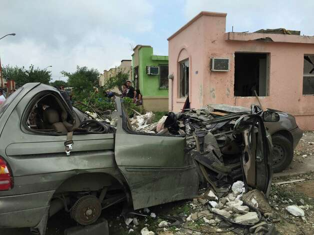 "People stand near a destroyed vehicle after a powerful tornado swept past  in Ciudad Acuna, northern Mexico, Monday, May 25, 2015. A tornado raged through the city on the U.S.-Mexico border Monday, destroying homes and flinging cars like matchsticks. At least 13 people were killed, authorities said. The twister hit a seven-block area, which Victor Zamora, interior secretary of the northern state of Coahuila, described as ""devastated."" (AP Photo) ORG XMIT: XMEX106 / AP"