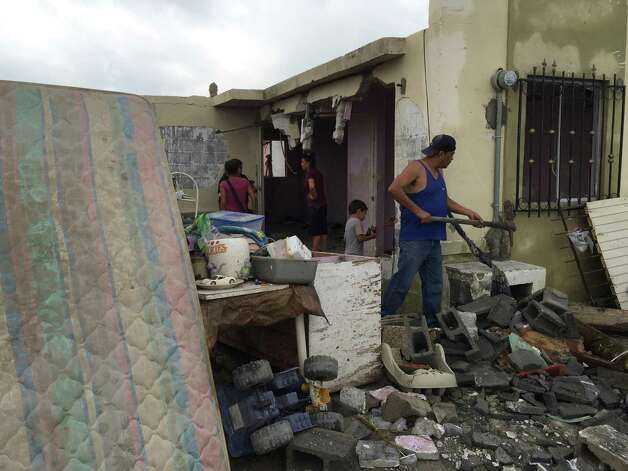 "Residents clear away debris from their home after a powerful tornado swept past in Ciudad Acuna, northern Mexico, Monday, May 25, 2015. A tornado raged through the city on the U.S.-Mexico border Monday, destroying homes and flinging cars like matchsticks. At least 13 people were killed, authorities said. The twister hit a seven-block area, which Victor Zamora, interior secretary of the northern state of Coahuila, described as ""devastated."" (AP Photo) ORG XMIT: XMEX107 / AP"