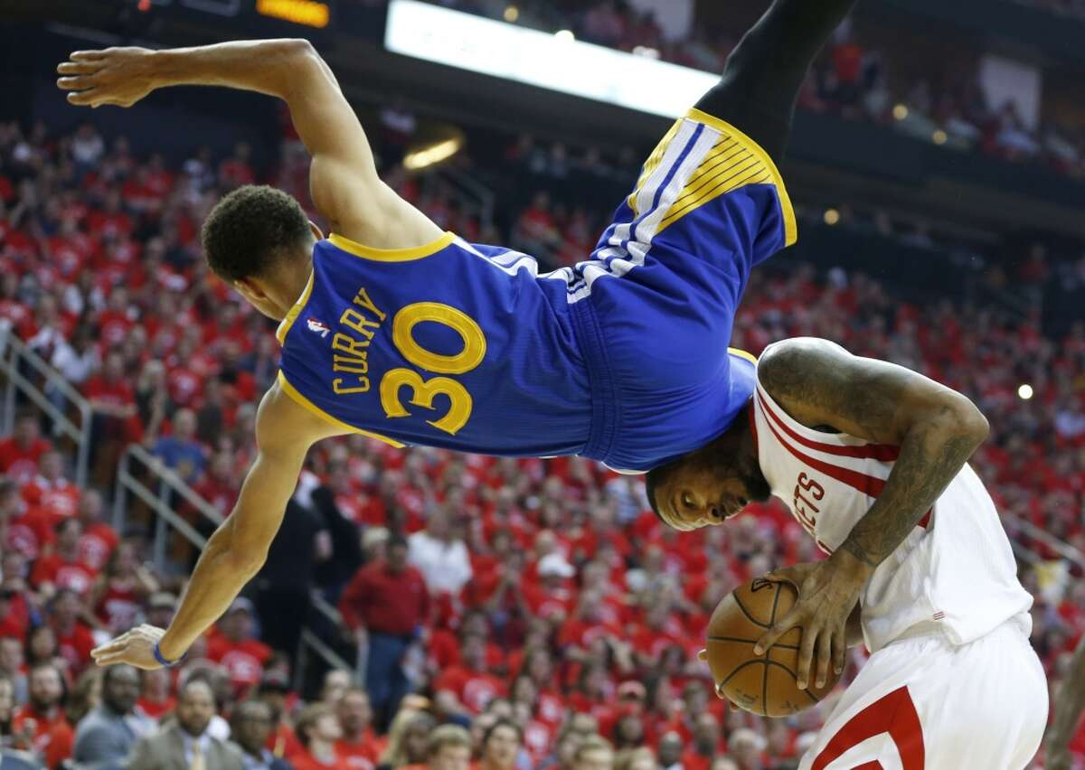 Golden State Warriors guard Stephen Curry (30) flies over Houston Rockets forward Trevor Ariza (1) attempting to defend a shot during the second quarter of Game 4 of the NBA Western Conference finals at the Toyota Center on Monday, May 25, 2015, in Houston. Curry fell to the floor and was taken from the game with an injury. ( James Nielsen / Houston Chronicle )