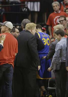 Golden State Warriors guard Stephen Curry (30) leaves the game after toppling over Houston Rockets forward Trevor Ariza during the first half in Game 4 of the Western Conference finals of the NBA basketball playoffs Monday, May 25, 2015, in Houston. (AP Photo/David J. Phillip)