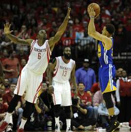 Golden State Warriors guard Stephen Curry #30 shots the ball as Houston Rockets forward Terrence Jones #6 defends in the third quarter of Game 4 of the Western Conference Finals, Monday, May 25, 2015, at Toyota Center in Houston, TX.