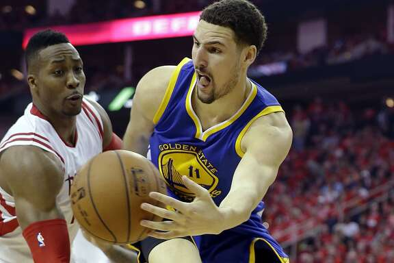 Golden State Warriors guard Klay Thompson (11) passes around Houston Rockets center Dwight Howard during the second half in Game 4 of the NBA basketball Western Conference finals Monday, May 25, 2015, in Houston. (AP Photo/David J. Phillip)