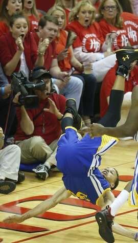 Golden State Warriors guard Stephen Curry (30) falls to the floor after toppling over Houston Rockets forward Trevor Ariza (1) during the first half in Game 4 of the Western Conference finals of the NBA basketball playoffs, Monday, May 25, 2015, in Houston. (Karen Warren/Houston Chronicle via AP) MANDATORY CREDIT