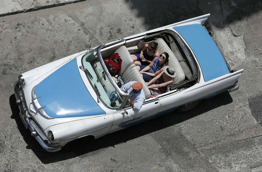 Tourists ride a classic American convertible in Havana, Cuba. The thaw in relations between the U.S. and Cuba has led to a dramatic 36 percent increase in visits by Americans to Cuba since January compared to the same period last year, along with a 14 percent rise in arrivals from around the world. = Photo: Desmond Boylan, Associated Press