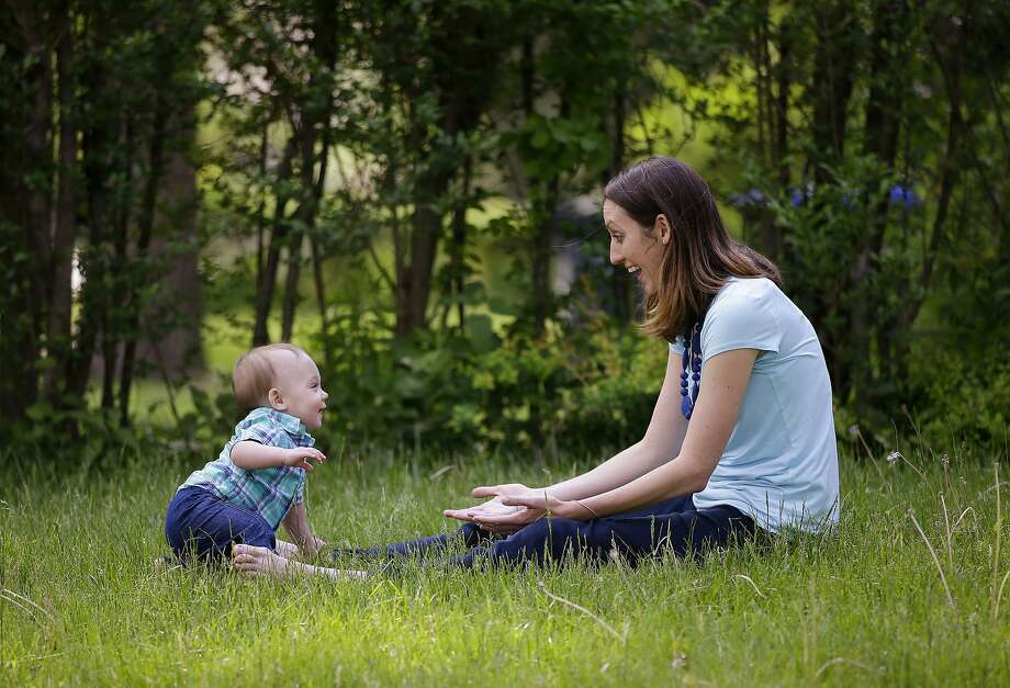 In this Friday, May 22, 2015 photo, Anne Quirk and her 11-month-old son Kieran play in the front yard of their home in Providence, R.I. Quirk had planned to take three months of unpaid leave from her job as a speech language pathologist after she gave birth but she needed five months off after her doctor ordered her on bed rest. (AP Photo/Stephan Savoia) Photo: Stephan Savoia, Associated Press
