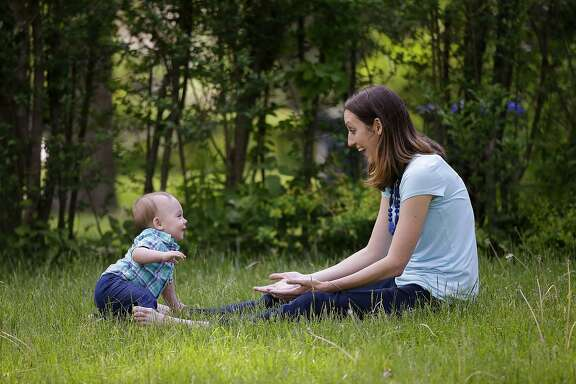 In this Friday, May 22, 2015 photo, Anne Quirk and her 11-month-old son Kieran play in the front yard of their home in Providence, R.I. Quirk had planned to take three months of unpaid leave from her job as a speech language pathologist after she gave birth but she needed five months off after her doctor ordered her on bed rest. (AP Photo/Stephan Savoia)