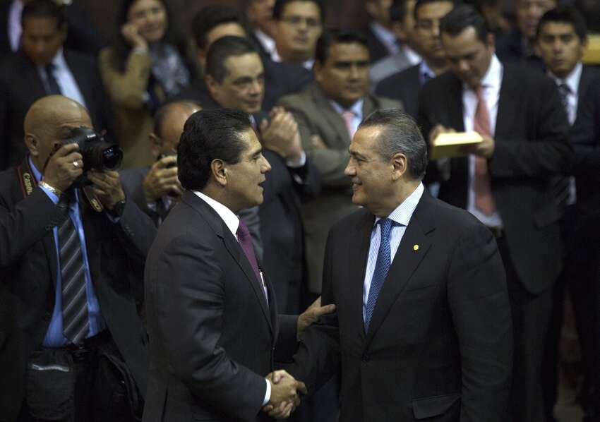 Manlio Fabio Beltrones (right), a deputy with the Institutional Revolutionary (PRI), shakes hands with Silvano Aureoles of the Party of the Democratic Revolution (PRD), after the final vote on a proposal to reform the oil industry at the Mexican Congress in Mexico City, Mexico, on Thursday, Dec. 12, 2013. Mexico will end 75 years of government control of its vast oil reserves after Congress approved the nation?'s most significant economic reform since the North American Free Trade Agreement.