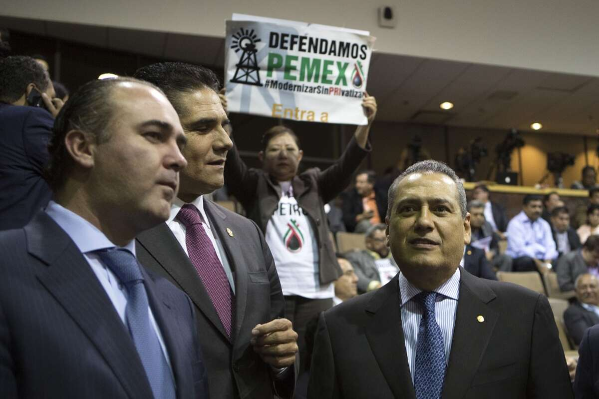 Manlio Fabio Beltrones (right), a deputy with the Institutional Revolutionary (PRI); Silvano Aureoles (center) of the Party of the Democratic Revolution (PRD); and Luis Alberto Villareal of the National Action Party (PAN), speak at the Mexican Congress in Mexico City, Mexico, on Thursday, Dec. 12, 2013. Mexico will end 75 years of government control of its vast oil reserves after Congress approved the nation?'s most significant economic reform since the North American Free Trade Agreement.