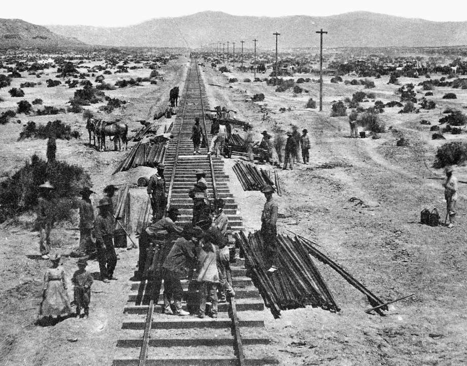 Track work takes place in Nevada as Central Pacific forces build the western link of the first transcontinental railroad, now a part of the Southern Pacific system, on May 10, 1868. Rail layers shown in the foreground were followed by groups of Chinese laborers who spaced and spiked the rail to the ties. Photo: Anonymous, AP