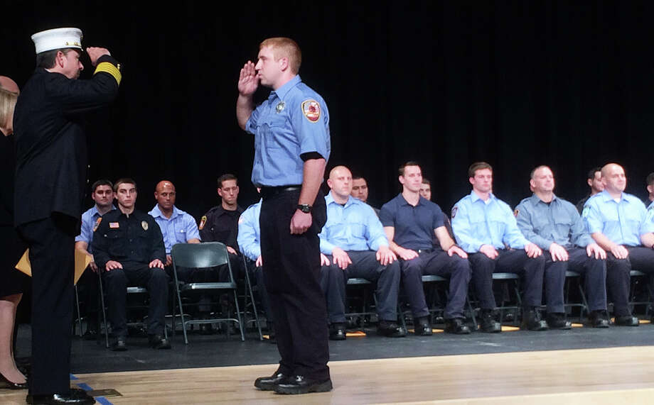 Recruit Firefighter Michael Peck, right, salutes Chief Andrew Kingsbury during recent graduation ceremony at the Connecticut Fire Academy. Photo: Contributed Photo / Westport News