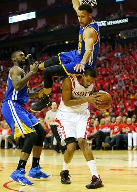 HOUSTON, TX - MAY 25:  Stephen Curry #30 of the Golden State Warriors falls over Trevor Ariza #1 of the Houston Rockets on his way to an injury in the second quarter during Game Four of the Western Conference Finals of the 2015 NBA Playoffs at Toyota Center on May 25, 2015 in Houston, Texas.  NOTE TO USER: User expressly acknowledges and agrees that, by downloading and or using this photograph, user is consenting to the terms and conditions of Getty Images License Agreement.  (Photo by Ronald Martinez/Getty Images) *** BESTPIX ***