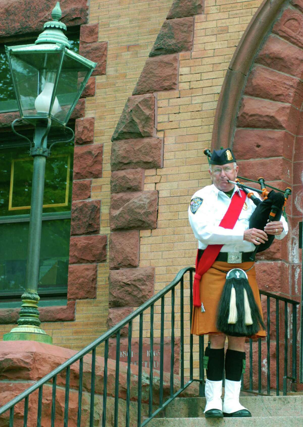 Patrick Maguire performs on bagpipes during the Memorial Day ceremony on the steps of New Milford Public Library, May 25, 2015