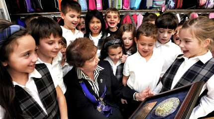 Sister Mary John O'Rourke, principal of St. Gregory the Great School in Danbury, shows the Blue Ribbon award the school received to first-graders including Gianna Casturan, left, Susan Radliff, center, Billy Murphy, center right, and Hailey Busse, right, Wednesday, Nov. 17, 2010.