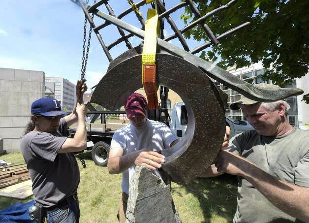 Artist John VanAlstine, center, installs a new piece of art on the front lawn of the Albany Institute of History & Art on Tuesday, May 26, 2015. (Skip Dickstein/Times Union)