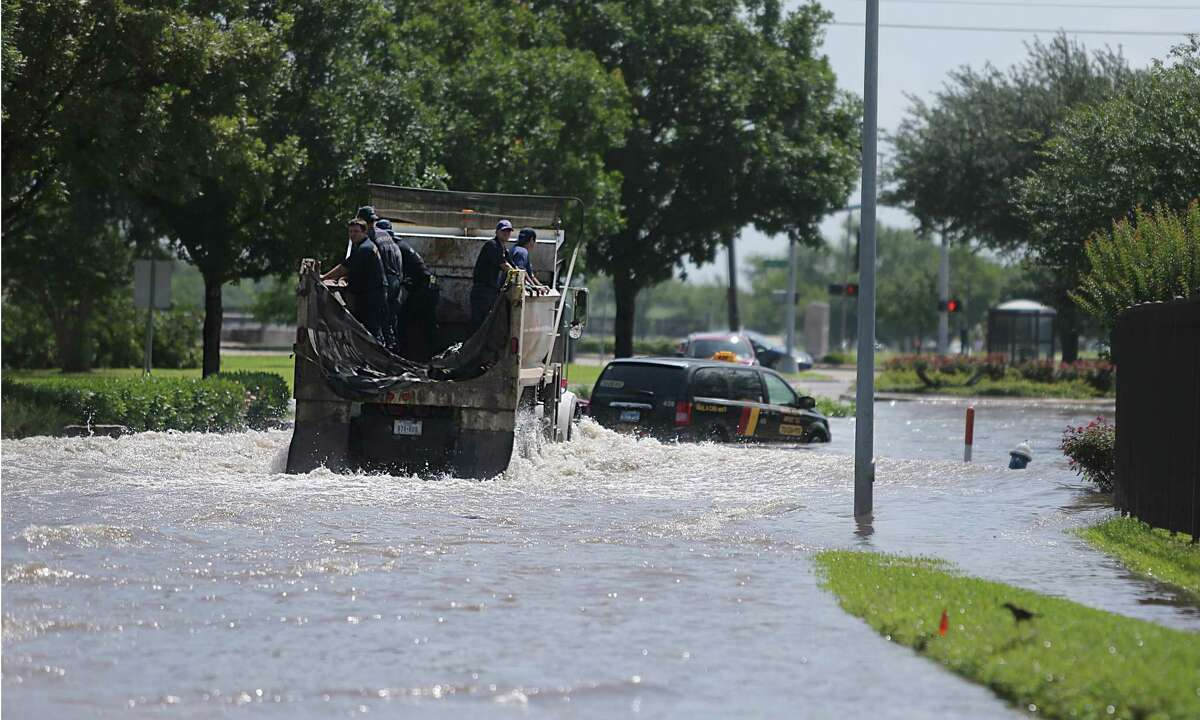 Houston Fire Fighters drive into flooded South Braeswood at Fondren. Brays Bayou is now within its banks, but neighborhoods are still flooded on Tuesday, May 26, 2015, in Houston.