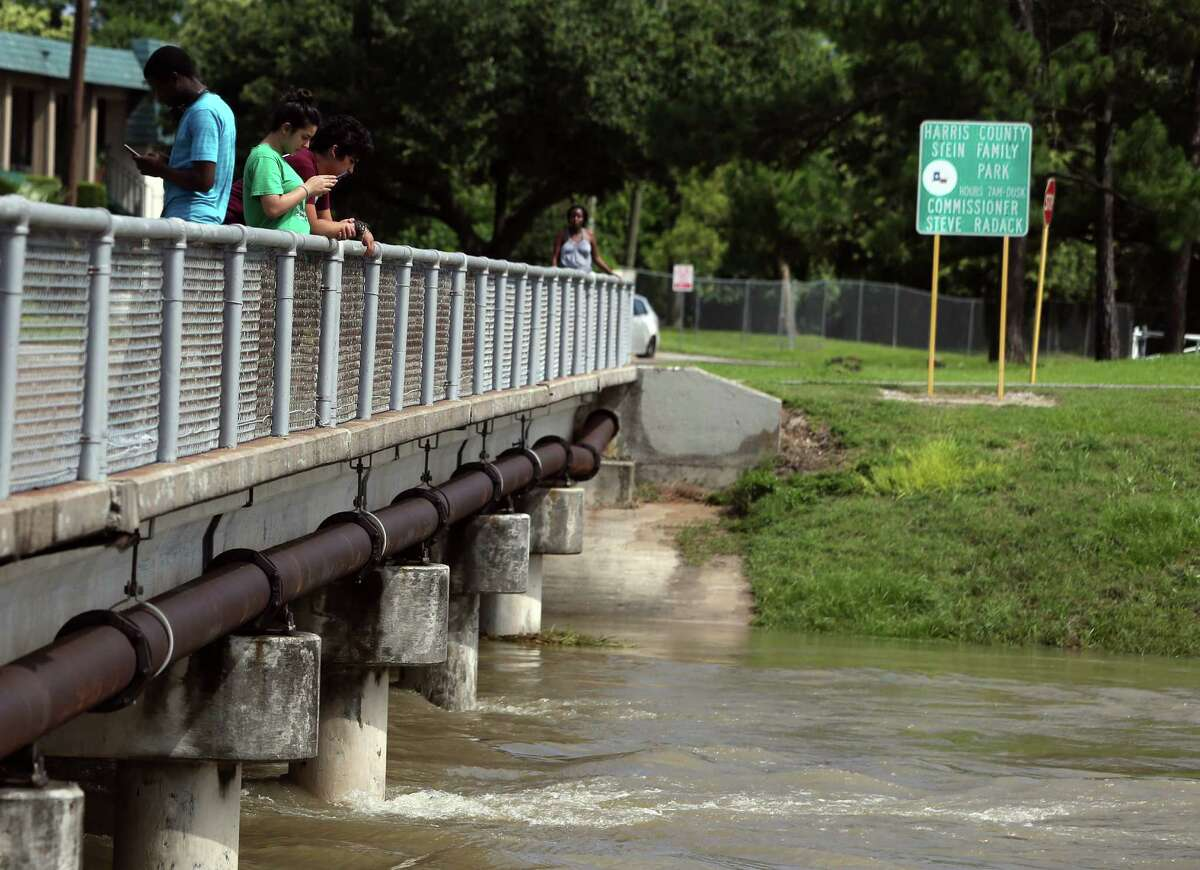 Spectators view Brays Bayou which overflowed its banks and flooded nearby neighborhoods along North Braeswood Blvd on Tuesday, May 26, 2015, in Houston.