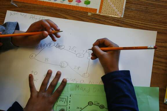 Second graders Miles White (hands l to r) and Dhyan Patel work together to solve a math problem at Argonne Elementary School during a math lesson on Tuesday, May 26, 2015 in San Francisco, Calif.