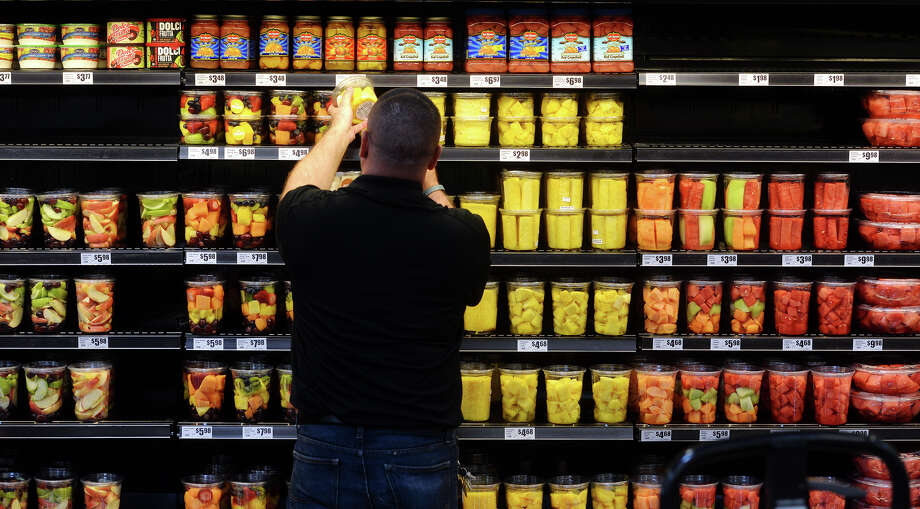An employee stocks one of the shelves in the produce section Tuesday. The new H-E-B location on College Street held a preview of their new store for the media and VIPs on Tuesday. The 56,000 square foot store will open to the public at 6 a.m. Wednesday. Photo taken Tuesday 5/26/15 Jake Daniels/The Enterprise Photo: Jake Daniels / ©2015 The Beaumont Enterprise/Jake Daniels