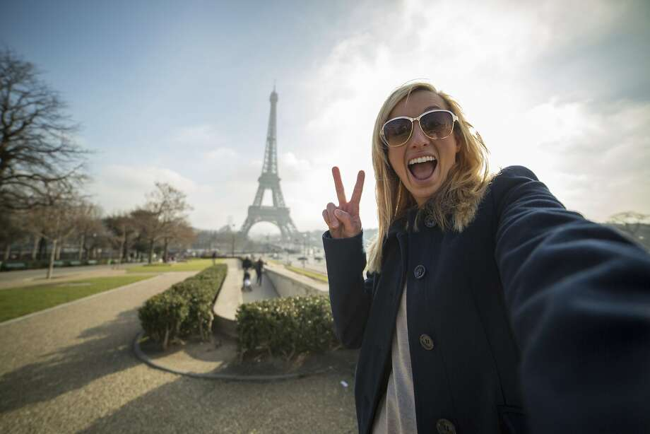 A playful woman's makes a peace sign in a selfie at the Eiffel Tower. Facebook has announced plans to open the Instagram feed to all advertisers. Photo: Getty Images
