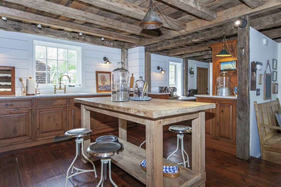 The kitchen has history-soaked wide plank floors and exposed ceiling beams. Photo: Contributed Photo / Darien News