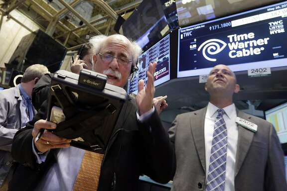 Trader Peter Tuchman, left, and specialist Jay Woods works the post that handles Time Warner Cable on the floor of the New York Stock Exchange, Tuesday, May 26, 2015.  Charter Communications is buying Time Warner Cable for $55.33 billion, creating another U.S. TV and Internet giant.v (AP Photo/Richard Drew)
