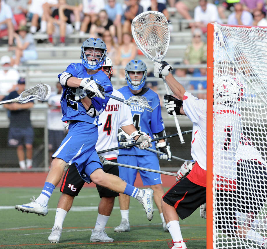Darien's Hudson Hamill, center, scores beating New Canaan goalie Drew Morris, right, during the boys FCIAC lacrosse semi-final match between Darien High School and New Canaan High School at Brien McMahon High School in Norwalk, Tuesday, May 26, 2015. Photo: Bob Luckey / Greenwich Time