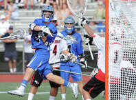 Darien's Hudson Hamill, center, scores beating New Canaan goalie Drew Morris, right, during the boys FCIAC lacrosse semi-final match between Darien High School and New Canaan High School at Brien McMahon High School in Norwalk, Tuesday, May 26, 2015.