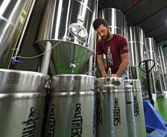 Russ Sealy, cellerman, fills containers of beer as Druthers Brewing Company opened for business Tuesday, May 26, 2015, on their new Broadway location in Albany, N.Y. This is their third location in the region.   (Skip Dickstein/Times Union) Photo: SKIP DICKSTEIN / 00031991A
