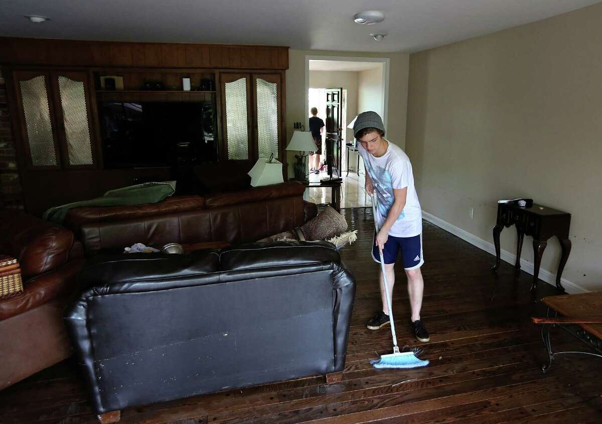 Lucas Martin sweeps water from the home at 5307 S. Braeswood on Tuesday, May 26, 2015 in Houston, TX The storm brought in two feet of water in their house and knocked down a tree in the front yard. (Photo: Thomas B. Shea/For the Chronicle)