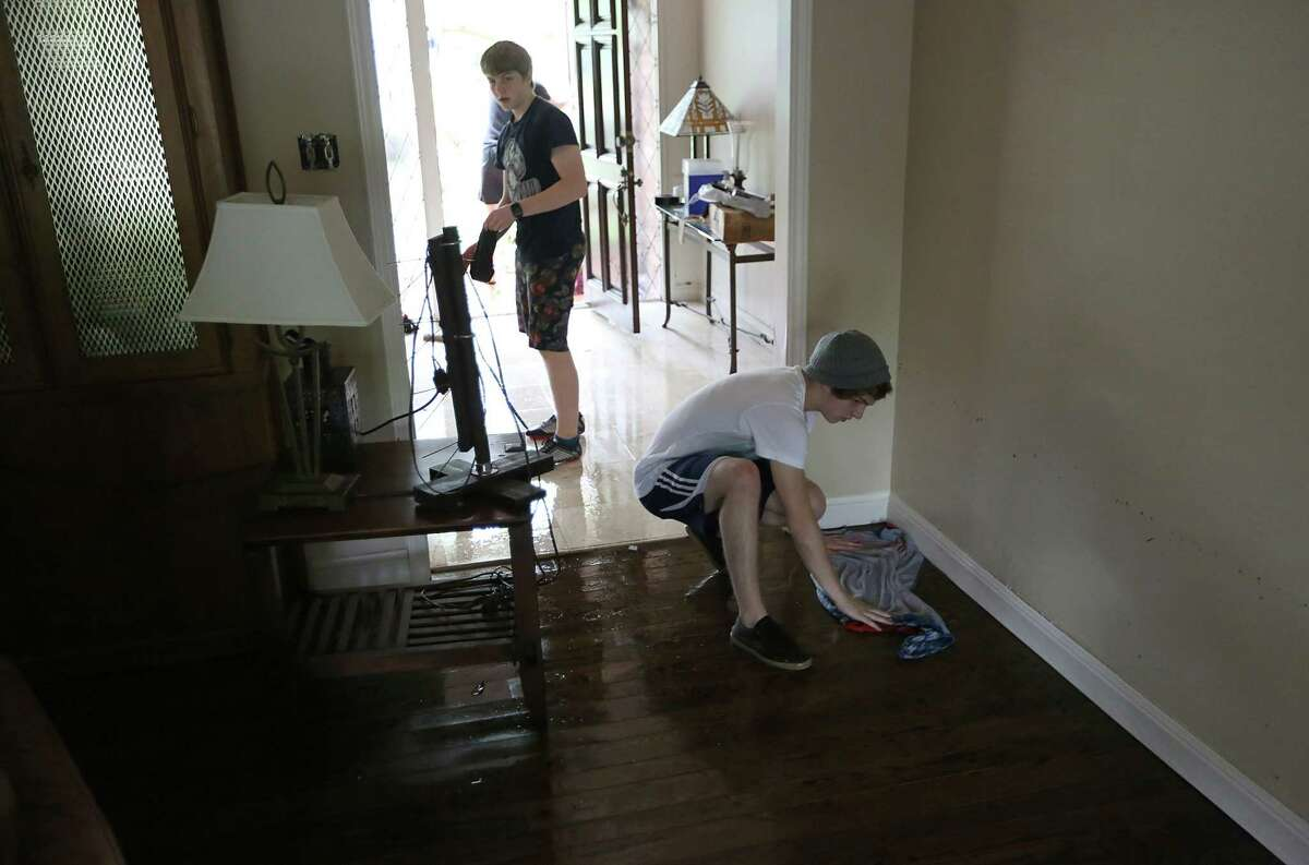 Lucas Martinwipes up water on the floor while his brother John Martins vacuums the water from the home at 5307 S. Braeswood on Tuesday, May 26, 2015 in Houston, TX The storm brought in two feet of water in their house and knocked down a tree in the front yard. (Photo: Thomas B. Shea/For the Chronicle)
