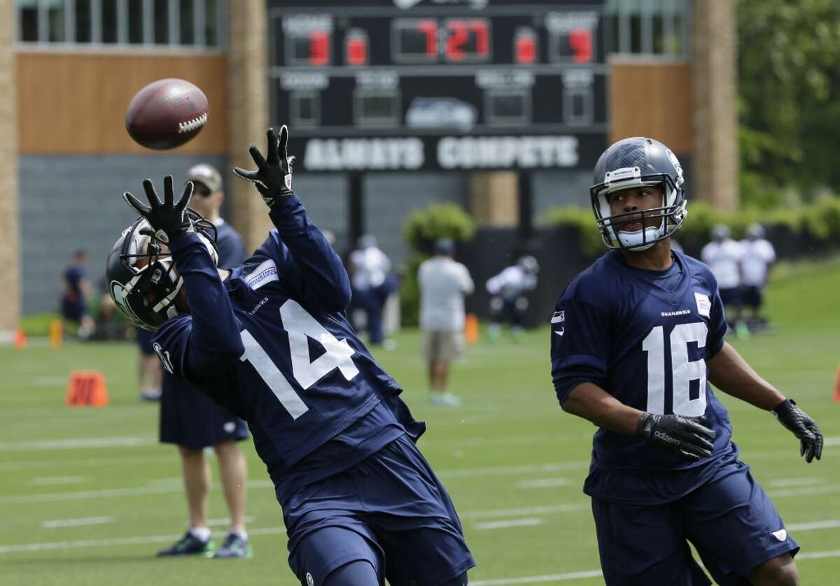 Seattle Seahawks rookie wide receiver Deshon Foxx (14) catches a pass as rookie wide receiver Tyler Lockett looks on at right, during an organized team activity Tuesday, May 26, 2015, in Renton, Wash. (AP Photo/Ted S. Warren)