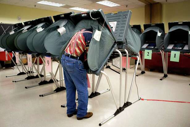 """Richard DeLosSantos, an election clerk, prepares voting booths at the Metropolitan Multi-Services Center in Houston last year.. The Supreme Court on Tuesday agreed to hear a case that will answer a long-contested question about a bedrock principle of the American political system: the meaning of """"one person one vote."""""""