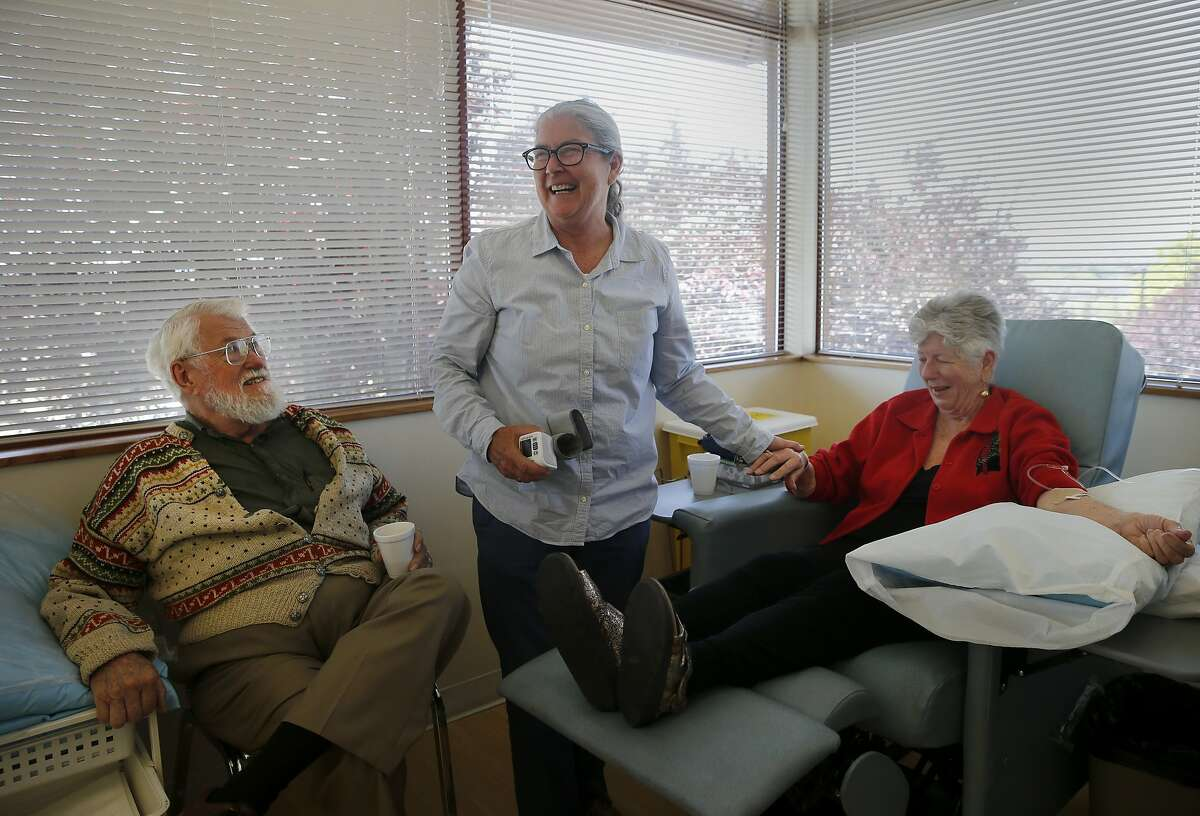 Study coordinator Terry Hess (center) stops to take the blood pressure of Carolyn McLeese (right) as Hess's husband Charles Rettke looks on Tuesday May 26, 2015. Carolyn McLeese is an Alzheimer's patient involved in the new clinical trial of new alzheimer's drugs which have showed some solid early-phase results. She is receiving an infusion at a St. Joseph Health facility in Santa Rosa, Calif.