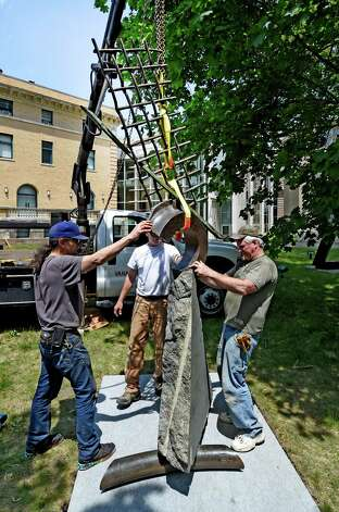 "With the assist of Nick Warner, left, and Bernie Dunn, right, sculptor John Van Alstine, center, works the crane at the Albany Institute of History & Art as he installed his sculpture ""Working the Sails"" (1990) in the Weir Sculpture Garden Tuesday afternoon, May 26, 2015 in Albany, N.Y. The sculpture is a bequest from the Estate of Philip M. Smith and it pays homage to the sailing vessels that have plied the Hudson River for centuries.   (Skip Dickstein/Times Union) Photo: SKIP DICKSTEIN / 00032005A"