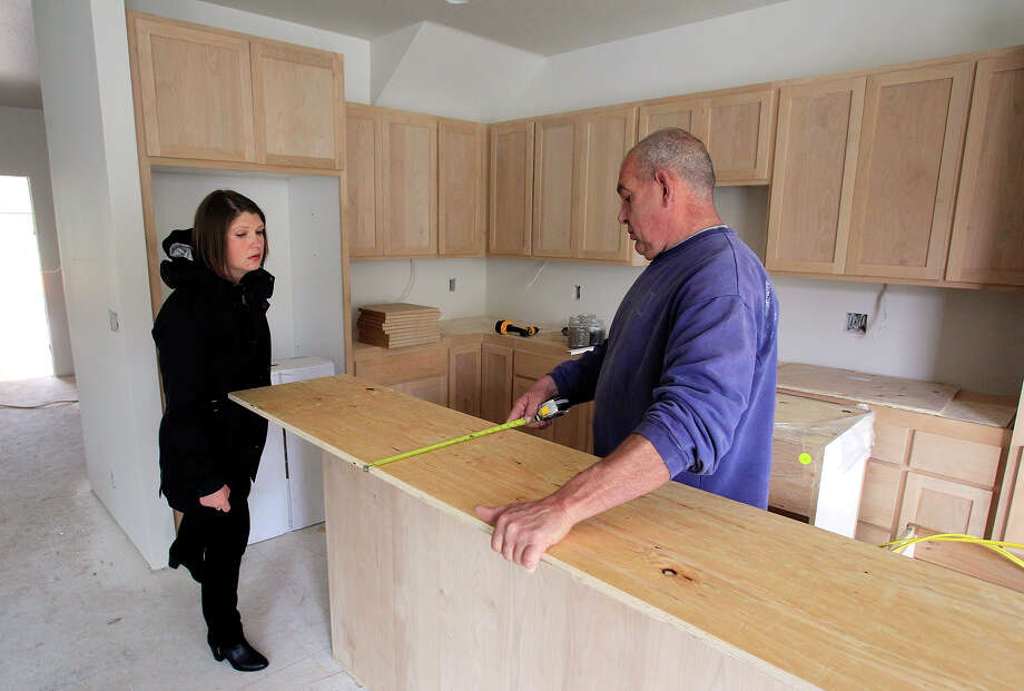 Mandi Butler of Future B Homes talks with finish carpenter Darrell Fosback at a home under construction in Eugene, Ore. More Americans bought new homes in April fresh evidence that the improved job market is powering the real estate sector. Photo: Paul Carter /The Register-Guard / The Register-Guard