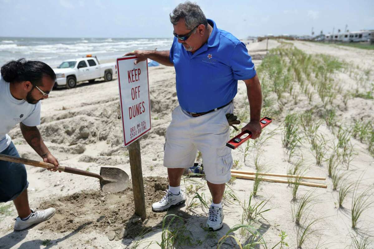 David Trevino and Joel Martinez, of the Galveston Island Park, install warning signs to stay off the newly nourished dunes
