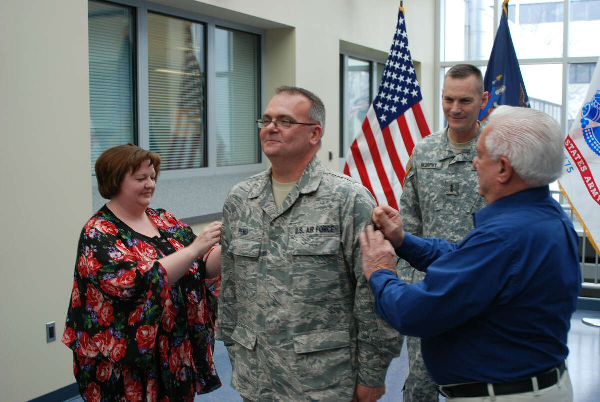 Division of Military and Naval ASffairs New York Air National Guard Senior Master Sgt. Shawn Peno receives his new rank from his wife Joan and father Peter during a promotion ceremony in Latham.