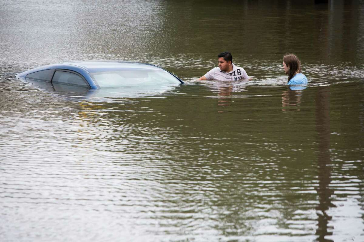 Roberto Salas, left, and Lewis Sternhagen check a flooded car on the frontage road between South Loop West Freeway and South Post Oak Road near the Willow Waterhole Bayou, Tuesday, May 26, 2015, in Houston. Floodwaters kept rising Tuesday across much of Texas as storms dumped almost another foot of rain on the Houston area, stranding hundreds of motorists and inundating the highways. (Marie D. De Jesus/Houston Chronicle via AP) ORG XMIT: TXHOU110