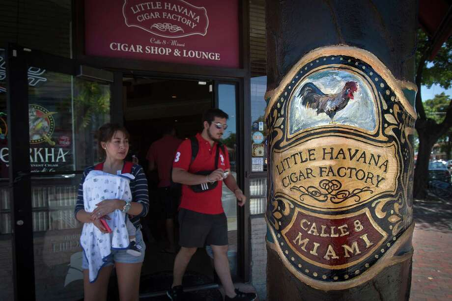 People walk out of the Little Havana Cigar Factory on SW Eighth Street (Calle Ocho) in the Little Havana area of Miami. Photo: Carlo Allegri /For The Washington Post / THE WASHINGTON POST