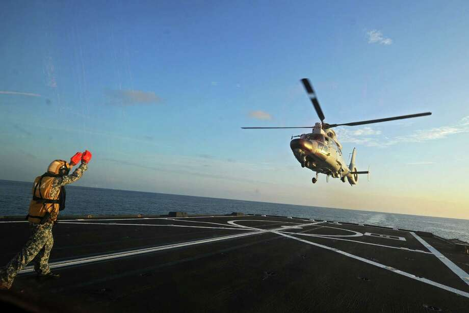 A Dolphin Z-9 helicopter from the Chinese navy flies off the deck of a Singapore navy vessel during an exercise. Photo: Then Chih Wey / Xinhua / Sipa USA