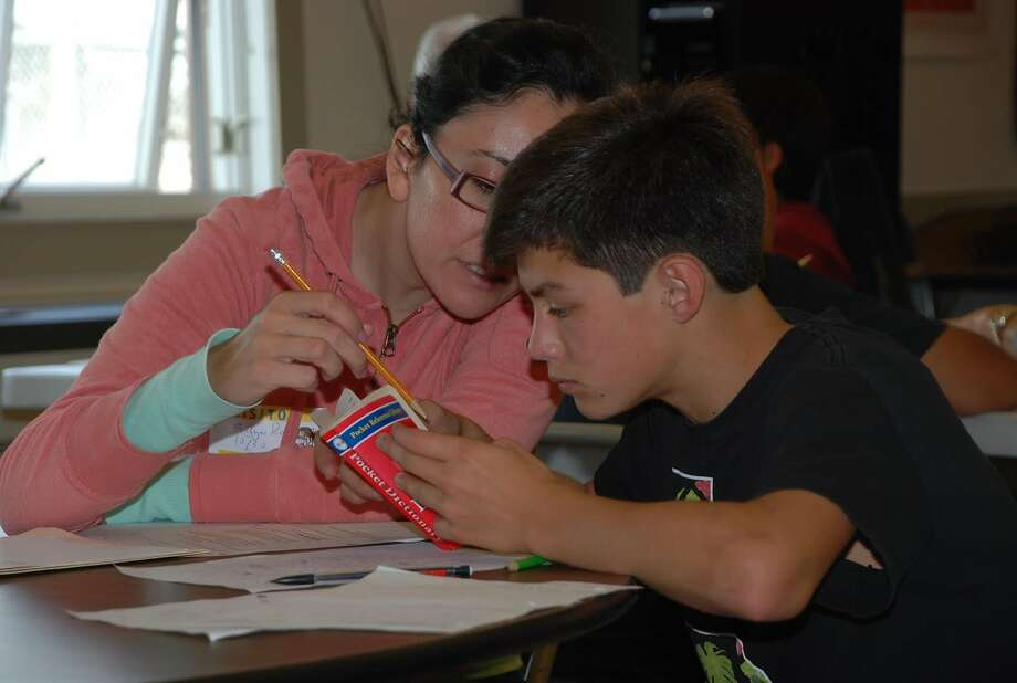 Coach Evelyn Rojo, left,  helps Kalani Kossa-Rienzi look up a word in the dictionary at Longfellow Middle School in Berkeley. Photo: Steven Cohen