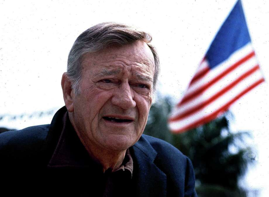 "This 1978 file photo shows actor John Wayne. Wearing a brown plaid coat worn by Wayne in 1945's ""Flame of Barbary Coast,"" Republican Lt. Gov. Dan Patrick has declared a day in honor of the quintessential screen cowboy as he presided over the Senate Tuesday, May 26, 2015. He declared it John Wayne Day in Texas to mark the Hollywood legend's 108th birthday and named the actor an honorary Texan. Photo: STF / AP"