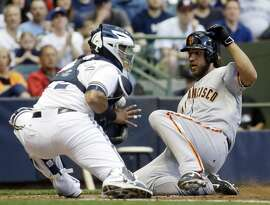 Milwaukee Brewers catcher Martin Maldonado can't handle the throw as San Francisco Giants' Madison Bumgarner slides safely home during the third inning of a baseball game Tuesday, May 26, 2015, in Milwaukee. Bumgarner scored on a hit by Joe Panik. (AP Photo/Morry Gash)