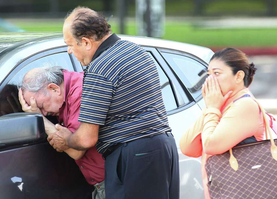 A man is comforted after finding out that a relative drowned in her truck at 5757 Ranchester near Harwin on Tuesday, May 26, 2015 in Houston, TX Photo: Thomas B. Shea, For The Chronicle / © 2015 Thomas B. Shea