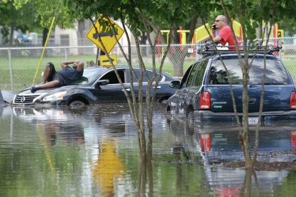Marcus Williams, left, and Robert Flores, right,  wait on top of their cars surrounded by water on South Gessner near South Bissonnet Tuesday, May 26, 2015, in Houston. It took more than 8 hours for them to both to be towed.