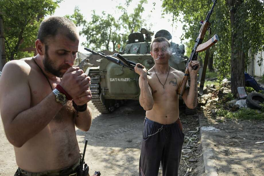 A Russia-backed rebel smokes, holding rifles in his both hands, on the outskirts of Donetsk, eastern Ukraine, Tuesday, May 26, 2015. The situation in eastern Ukraine has remained tense and skirmishes between Ukrainian forces and Russia-backed separatists have continued despite a cease-fire signed in February. Photo: Mstyslav Chernov, Associated Press
