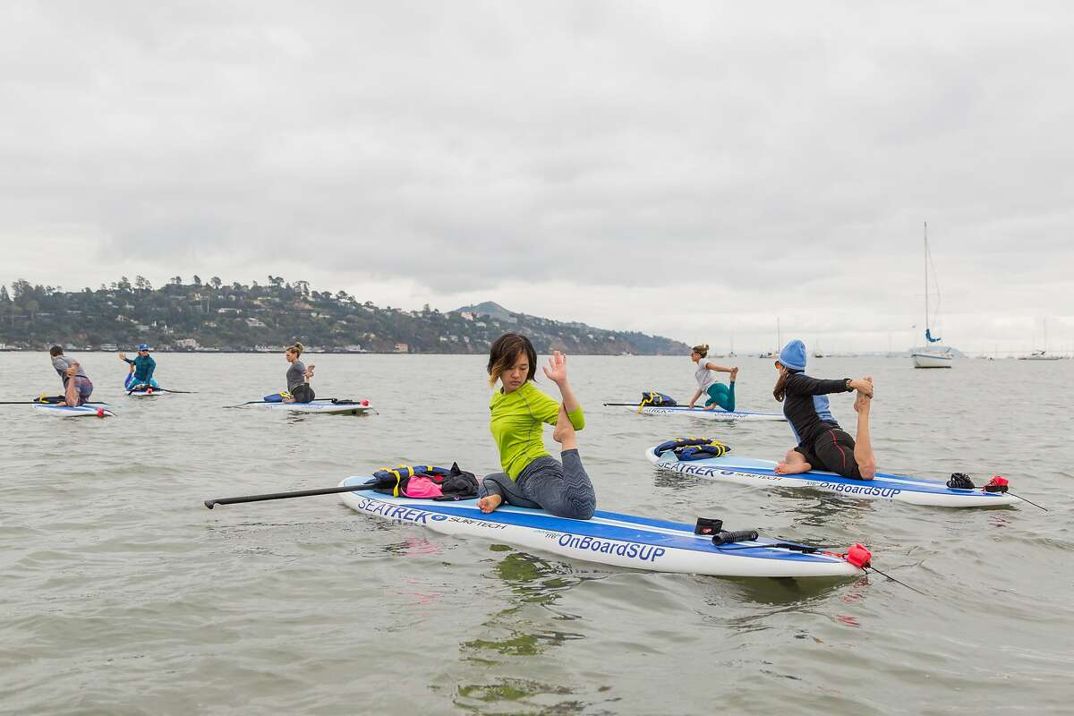 Maple Sunghitakul while doing stand-up paddle board yoga in Richardson Bay led by Sea Trek where yogi Leigh Claxton started the trend in 2008 in Sausalito, Calif., Wednesday, May 20, 2015.