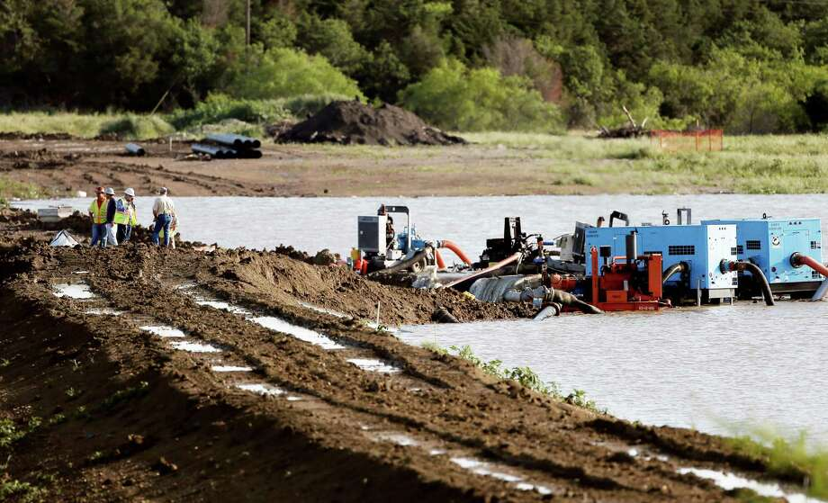 Workers attempt to relieve the pressure from the earthen dam at Padera Lake, Wednesday, May 27, 2015, in Midlothian, Texas.  Water was flowing over the top of the  dam early Wednesday morning following days of heavy rain. Police say emergency personnel could shut down a highway if the dam, southwest of Dallas breaks. (AP Photo/Brandon Wade) Photo: Brandon Wade, Associated Press / FR168019 AP