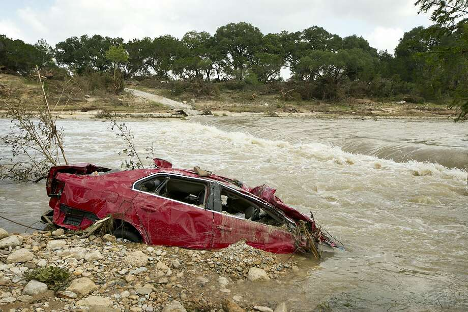 A destroyed car is submerged in the Blanco River in Wimberley, Texas, after the flood on Tuesday May 26, 2015. Photo: Jay Janner, McClatchy-Tribune News Service